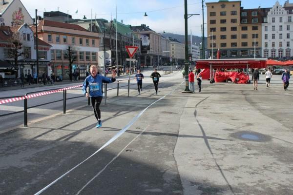 Arvid Tangerås vinker til fotografen på vei over Torget.