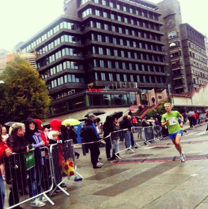 Innspurten på Rådhusplassen under fjorårets Oslo Maraton. Christian Fredriksen løper inn på tiden 1,14,14 på halvmaraton, hans nest raskeste halvmaratonløp noensinne i grått regnvær. I morgen er det meldt sol og mange flere tilskuere! Foto: Fra bloggen