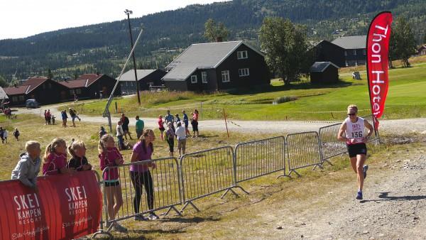 Astrid Uhrenholdt Jacobsen har kun den siste lille bakken igjen og heies mot mål av elevene i hennes egen sommerskiskole.