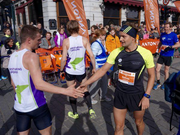 Fornøyde lagkamerater fra Kristiansand Løpeklubb med Andreas Mathingsdal Pedersen til høyre, gratulerer hverandre med innsatsen. Han løp på 33.38 og ble nr. 61. Foto: Thomas Stordalen / Sportsmanden.no